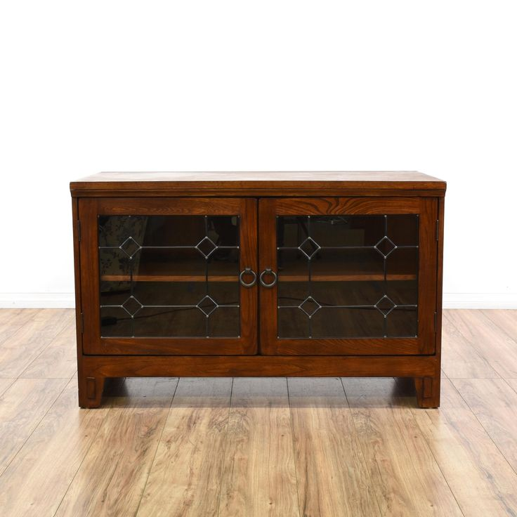 This mission style media cabinet is featured in a solid wood with a glossy cherry finish. This craftsman style entertainment center has 2 glass front doors with diamond print mullions and a large interior cabinet with shelving. Perfect tv stand with space for electronic components!  #countryfarmhouse #storage #mediacenter #sandiegovintage #vintagefurniture