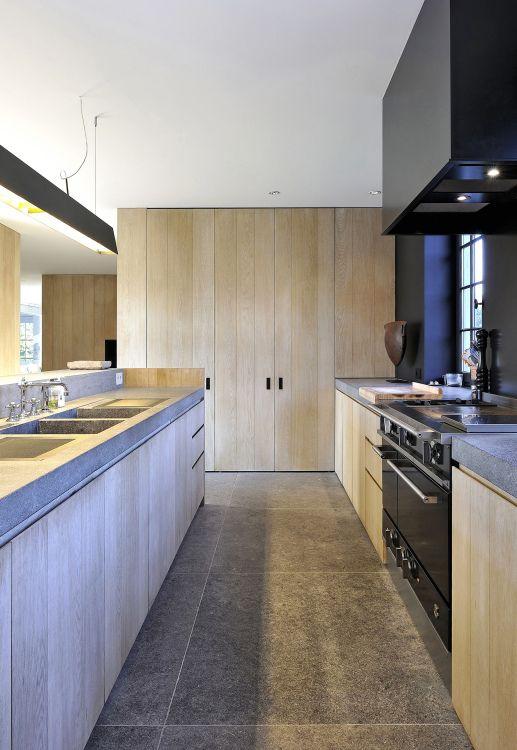 De keuken is het bruisende centrum van een woning geworden. Koken, aperitieven, gezellig tafelen, ontspannen, werken, … de functies zijn oneindig. In deze landelijke keuken zorgt het verticale lijnenspel voor de strakheid terwijl de materialen gezelligheid garanderen. Deuren in dik eik fineer (naturel afgewerkt), tablet in blauwe hardsteen en accenten in zwart.Architect: Vincent Van Duysen