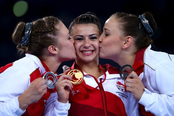 Claudia Fragapane of England is kissed on the podium by Ruby Harrold and Hannah Whelan after winning the Women's All-Around Final at the SECC Precinct during day seven of the Glasgow 2014 Commonwealth Games on July 30, 2014 in Glasgow, United Kingdom.