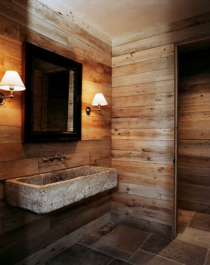 Antique boards used as paneling in the bathroom. 18th-century stone basin. Photo: Francois Halard.