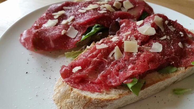 Ambachtelijke witbrood belegd met carpaccio, parmezaanse kaas, peper en zout, op een bedje van salade.