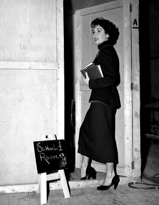 "sparklejamesysparkle: "" Elizabeth Taylor heads to class on the MGM set of The Conspirator, photo by Virgil Apger, 1949. In her last year of high school at the time, Elizabeth was required by law to attend school for a minimum of three hours per day..."