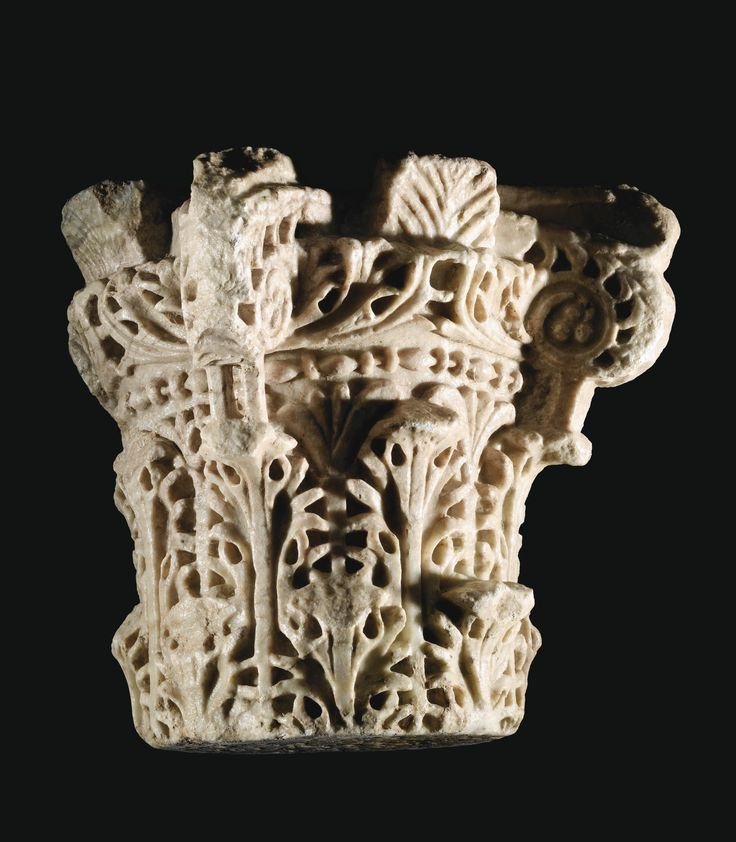 An Umayyad marble capital, Cordoba, Spain, Period of Al-Hakam II (961-976 AD) of pale stone, the surface deeply carved and drilled with three layers of acanthus leaves supporting scrolling wreaths extending out of the corners, between four palmettes on each side and a vegetal border 33cm. height.