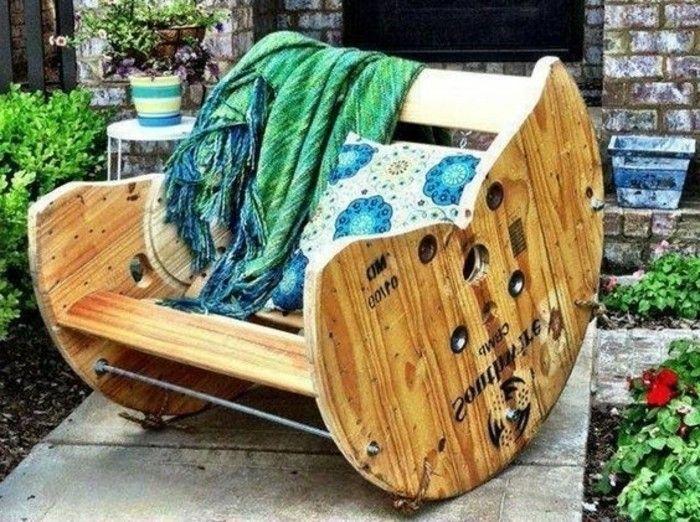 fauteuil touret dans un jardin, exemple de coin repos a l exterieur, coussin à motifs floraux et couverture