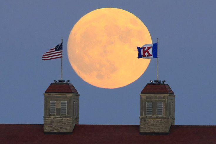La luna se eleva sobre las banderas en la Universidad de Kansas (EE UU).