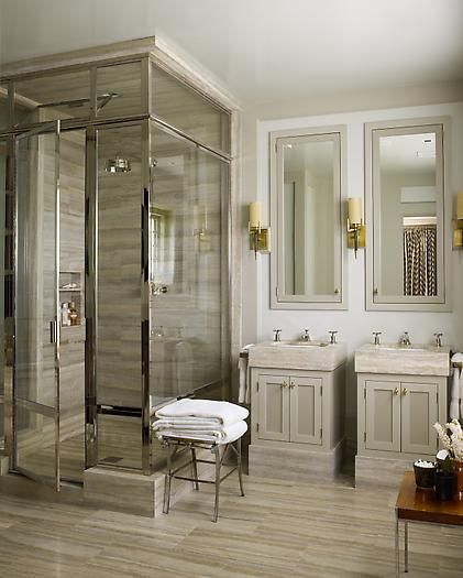 Soft muted grey bathroom cabinets. Shower is given a glamorous lift using thick silver/chrome frames around the glass. Floor tiles have a stripe running through them adding visual width to the bathroom. Mirror cabinets provide additional storage