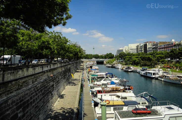 A view looking down the Port de l'Arsenal towards the July Column at the end, showing the many boats moored up along the port.  More photos to be seen at www.eutouring.com/images_port_de_l_arsenal.html