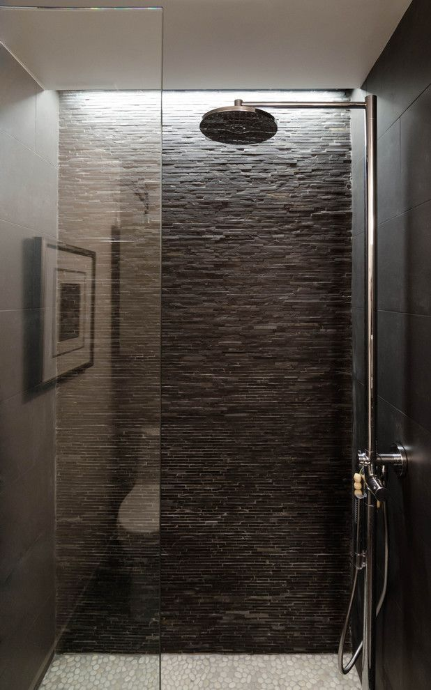 Pebble flooring is paired with stacked stone walls makes you feel like you are showering in nature!  exposed piping running up the wall to the showerhead is really  great look.  lighting up at the ceiling, gives you great light in the shower.: