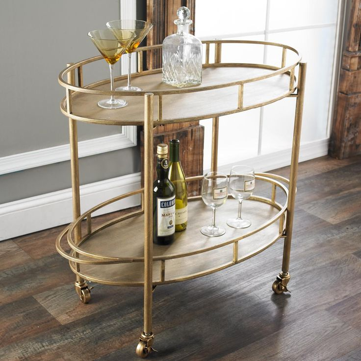 """Oval Bar Cart Impress your guests with this smart oval serving cart on locking casters. The brushed gold finish with black undertones will go anywhere for impromptu entertaining or everyday storage and display. (30.5""""Hx34.5""""Lx17.88""""W)"""