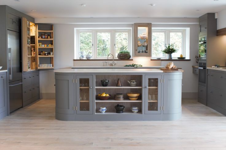 A beautiful open plan barn conversion with a shaker kitchen painted with Farrow & Ball Mole's Breath. Open shelving with glass fronted cabinets on a curved centre island topped with marble worktops. An open larder cupboard and glazed cabinet with internal lighting add a pop of brightness.