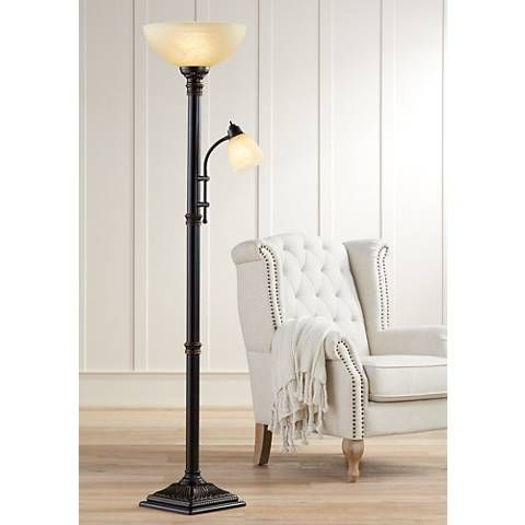 In an oil rubbed bronze finish, this torchiere floor lamp is paired with amber glass shades and features a reader arm for targeted task lighting.