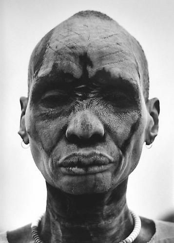 Sebastiao Salgado, Dinka man at the cattle camp of Kei. People cover themselves with ash to sterilize the skin against insects and parasites, Southern Sudan, 2006, gelatin silver print: