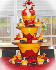 We had a blast making this Hunny Pot Cupcake stand for this Winnie the Pooh themed birthday party.  By:The Crafty Host Blog by Port City Event Planners #winnethepooh #cupcakestand #kidsbirthdayparty #tigger #pooh #hunnypot #kidsparties