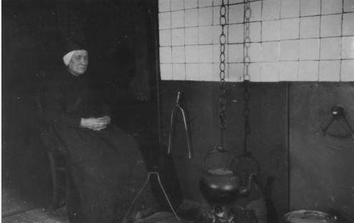 Dame in klederdracht bij de schouw met een open haardvuur in haar woning te Ees. Op de foto een waterketel aan een ketting. Foto Mevr. Bergman-Beins 1899-1919 Drents Archief #Drente