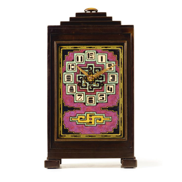 A copper and enamel mantel clock designed by J. Eisenloeffel 1928 the rectangular case with a stepped finial crowned with a cabochon stone, incorporating a dial with abstract ornaments in shades of purple, turquoise, yellow, black and white unmarked height 40 cm