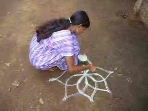 girl drawing rangoli pattern