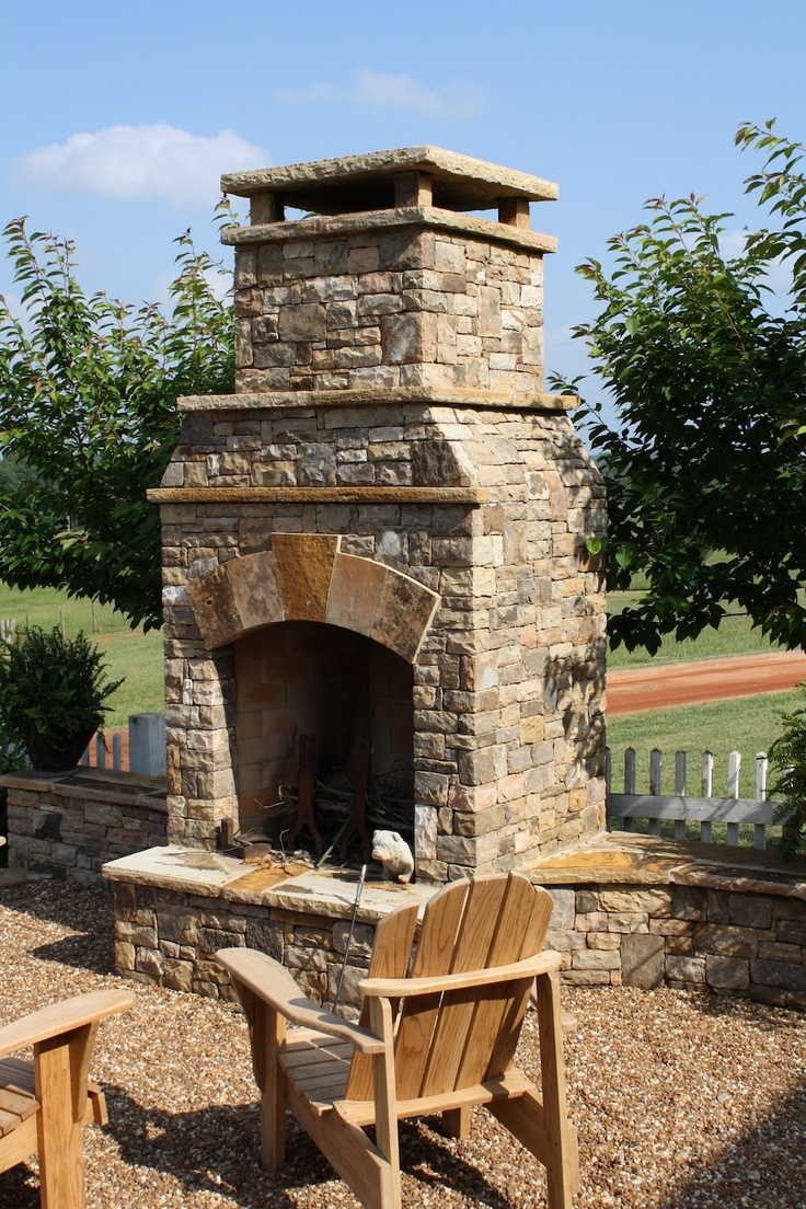 Outdoor Stacked Stone Fireplace With Attached Seating Walls