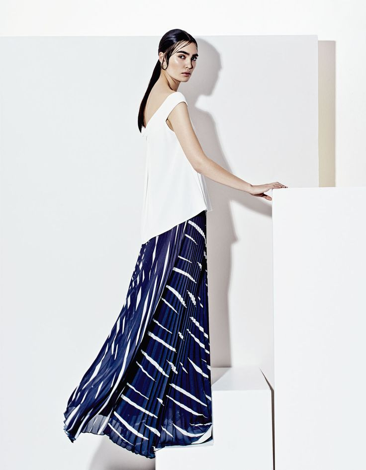 Elegant white long blouse and abstract printed skirt, futuristic style