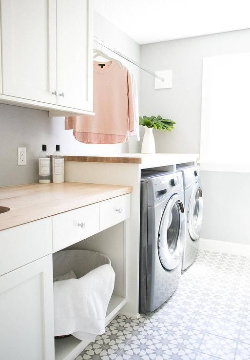 White and gray laundry room clad in white and gray cement floor tiles features a gray front loading washer and dryer enclosed beneath a butcher block countertop fixed below a tension drying rod and also accenting white cabinets positioned against a gray wallpapered wall.