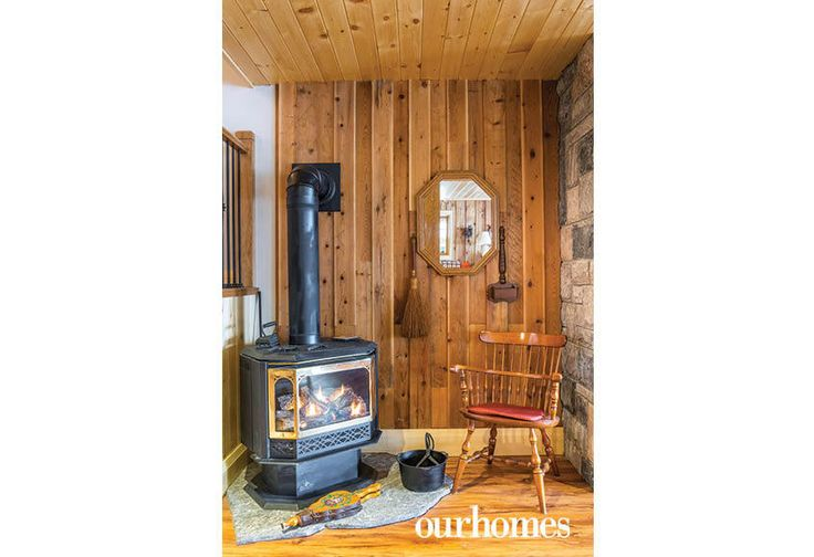 """The propane stove from the old cottage burns brightly in the new lake house. Pine wall panelling was salvaged from the original cottage.    See more of this home in """"Fifth Generation Legacy on Muskoka's Moon River"""" from OUR HOMES Muskoka Early Summer 2017: http://www.ourhomes.ca/articles/build/article/fifth-generation-legacy-on-muskokas-moon-river"""