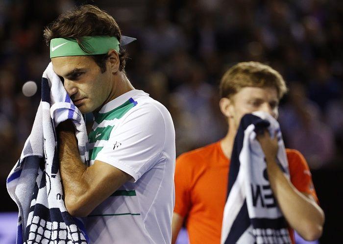 Roger Federer walks past David Goffin.