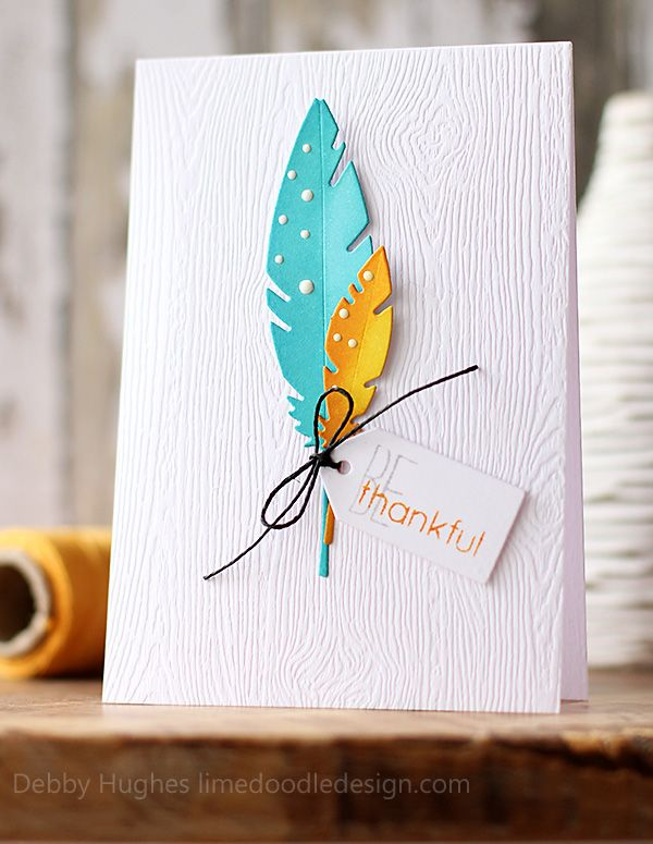 handcrafted Thanksgiving card ... by Debby Hughes ... non-traditional look ... clean and simple ... white card with wood grain embossing  ... die cut feathers in turquoise and yellow/orange ... white enamel dots ... tag with sentiment ... awesome!!