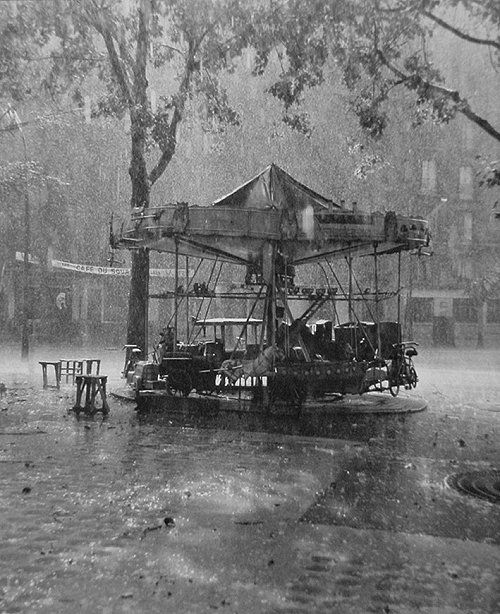 This is a truly lovely photograph by Robert Doisneau (1912-1994).  This is one of the great photographs of rain, capturing emotions associated with the weather and its effects on the empty, childless merry-go-round.