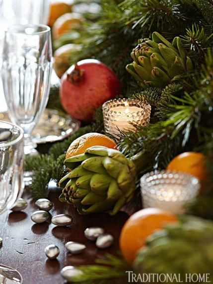 Greenery, pomegranates, oranges, artichokes, and silver almonds fashion a colorful centerpiece. - Traditional Home ®/ Photo: Eric Plasecki / Design: Timothy Corrigan