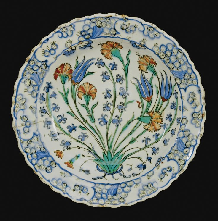AN IZNIK POLYCHROME DISH, TURKEY, CIRCA 1560-1570 of shallow rounded form, decorated in underglaze cobalt blue, viridian green and relief red, outlined in black, with a base foliate motif issuing five carnations and three sprays of small stylised hyacinths, the rim with circular and spiral motifs, the reverse with alternating rosettes and tulip pairs