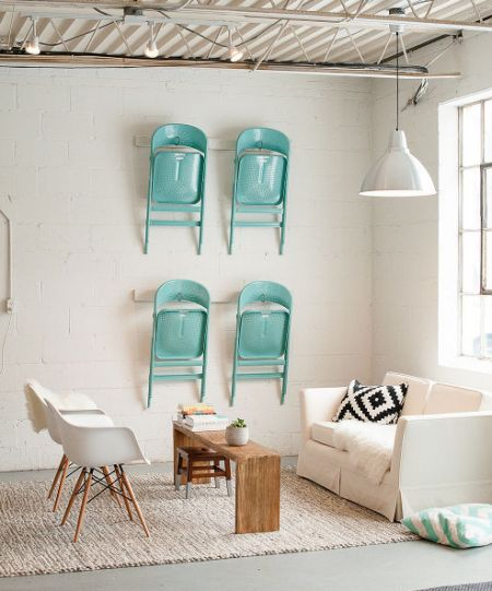 Loving the idea of saving space and hanging the extra chairs on the wall a lovely color too