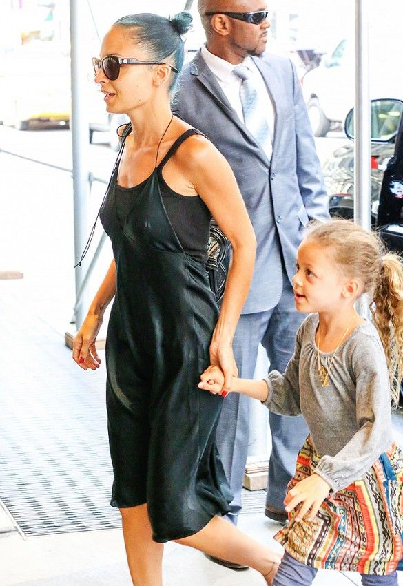 Nicole Richie wears a black tank layered under a black halter dress with daughter Harlow Madden