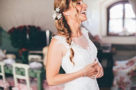 Acconciatura sposa laterale con treccia spettinata e fermaglio con fiori