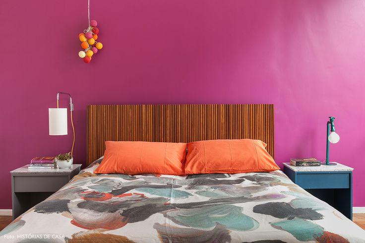 Quarto de casal com cama de madeira, parede roxa e roupa de cama estampada.