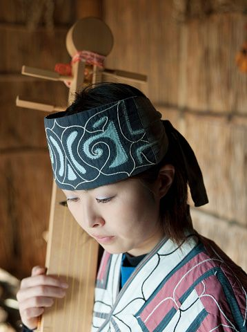 An Ainu woman playing a Tonkori in the Ainu Museum. The Ainu people are indigenous to Japan and Russia. Lake Poroto, Hokkaido, Japan