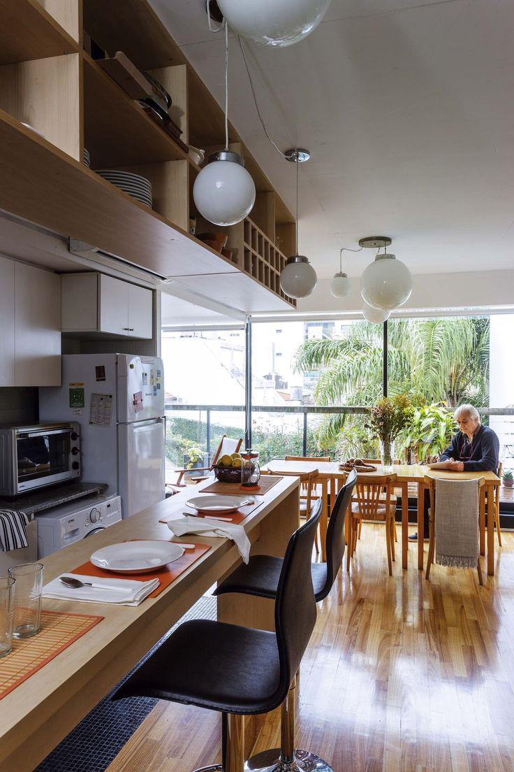 Cocina integrada al comedor de un departamento con piso de eucalipto, barra enchapada en madera y mueble colgante a tono.
