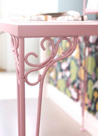 Scrivania rosa con dettagli decorativi.