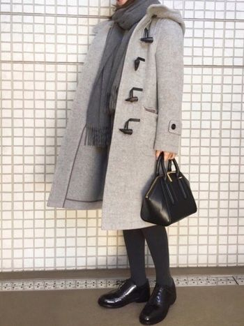 杢グレーのコートに、濃グレーのストールとタイツ、黒のシューズとバッグ。トーンの異なる無彩色を合わせて、単調にならないように計算された上級グラデーションコーデ。
