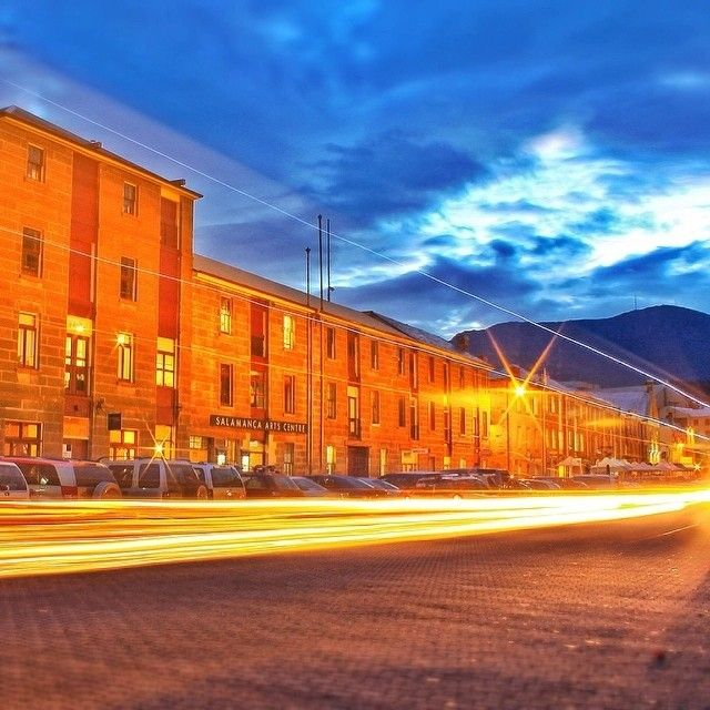 Night lights in Hobart's Salamanca Place. The iconic warehouses were built by convicts in the 1830s using sandstone quarried on site.Today they house an eclectic range of cafes, restaurants, artisan retail outlets, art galleries and performance spaces, and form the backdrop to Hobart's famous weekly Salamanca Market. #salmanca #tasmania #discovertasmania #hobart Image Credit: Kathryn Leahy