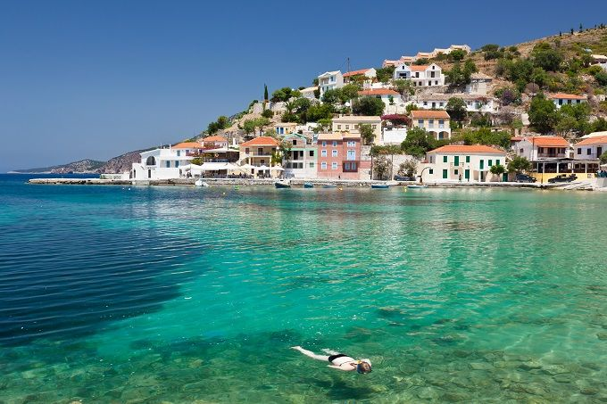 Kefalonia, Greece, White-washed buildings in a bay, blue sea.