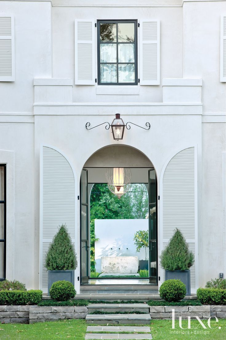 the large scale of the home u2019s elegant arched entryway provides a dramatic first impression of