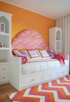 Girl's rooms - orange walls, white pink orange chevron rug, white Hollywood Regency daybed, orange pink headboard, pink velvet pillows, purple silhouette pillows and white bookshelves #kidsroom #girlbedroom #orangeinspiration Find more inspirations at www.circu.net