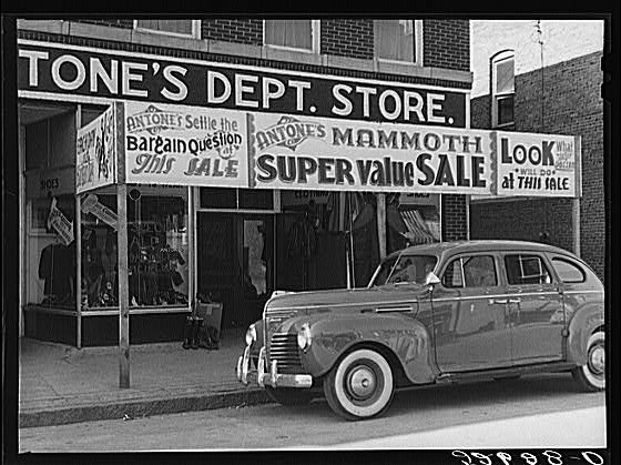 Signs on store windows advertising sales during tobacco auction time in Zebulon, Wake County, North Carolina