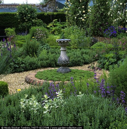 Herb Garden. Sundial on chamomile circle. Edged in box, teucrium or origanum, beds of herbs - mint, lavender, fennel, catmint, rosemary, marigold and rue. Gravel paths - Coton Manor