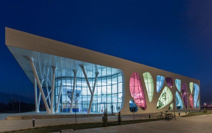 Pista de patinaje en Kayseri (Turquía). Moderno edificio en Turquía con una pista de hielo para patinar. Destaca por la impresionante fachada con grandes ventanales amorfos de colores, y los soportes inclinados de la entrada. Descripción y planos.      #Arquitectura
