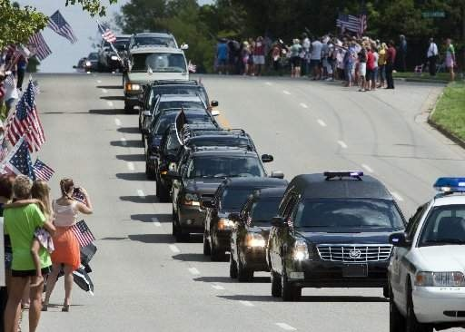 The procession carrying the remains of Navy SEAL David Warsen travels along 68th Street SE in Grand Rapids, Mich., Monday, Aug. 27, 2012. Warsen, an East Kentwood High School graduate, died August 16, 2012, in Afghanistan when a Blackhawk helicopter went down.