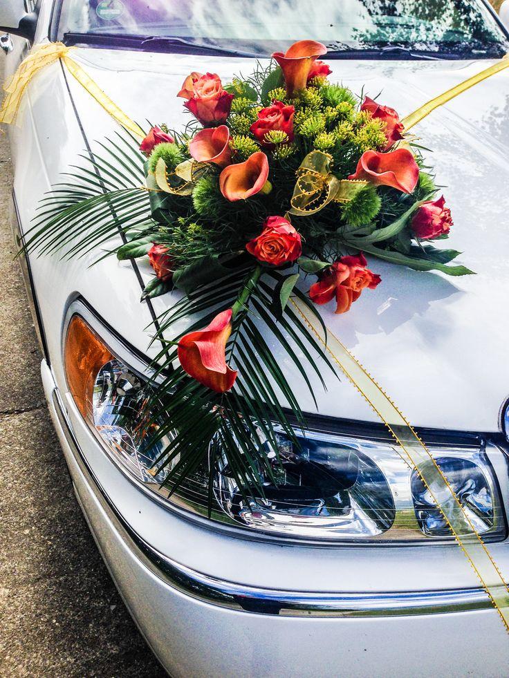 Calla Blumengesteck auf der Motorhaube in Orange Gelb für das Hochzeitsauto