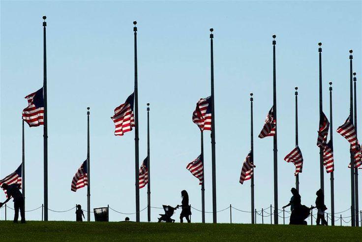 Pessoas passam pelas bandeiras nacionais que voam a meio mastro no Monumento de Washington em Washington, DC, em 11 de setembro de 2015.   Como parte das comemorações em todo o leste dos Estados Unidos das solenidades  de 11 de setembro de 2001.