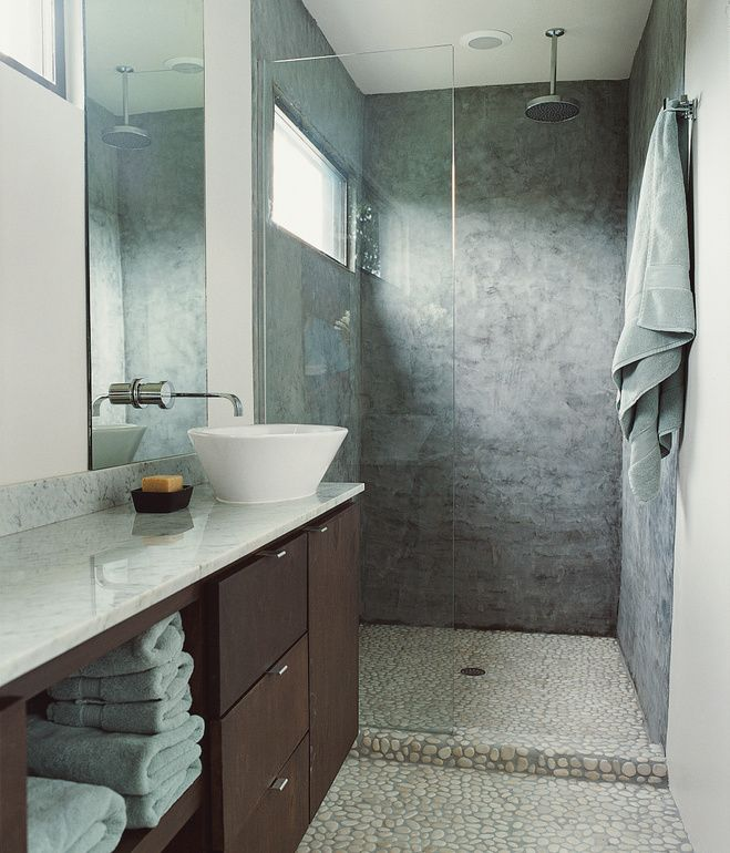 ... Predominate In The Bathroom, With Walker Zanger Stone Floors  Complemented By Sanded Concrete Walls And Dark Mahogany Cabinets Topped By  A Slab Of White ...