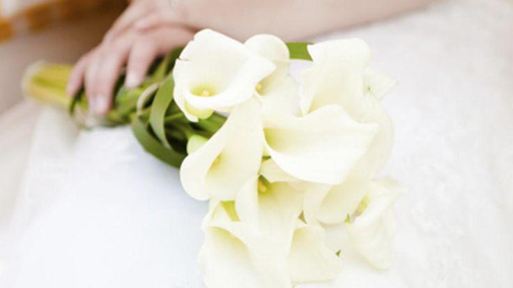 Bruid gehuld in pure witte kleuren op haar trouwdag.