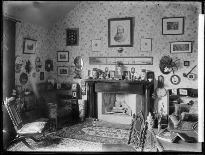 Sitting room interior, probably in Wanganui, circa 1900. Shows the area around a fireplace, with chairs alongside, and carpets on the floor. The mantelpiece holds a row of objects. Examples of Japanese pottery can be seen. The walls are covered in a floral paper in an art nouveau style and decorated with framed photographs and paintings. On a table in the right foreground, by a vase of snowdrops, is a Royal Academy New Gallery Pictures catalogue dated 1893. Photograph taken by Frank J…